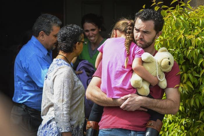 Rusty Page carries Lexi while Summer Page, in the background, cries as members of family services, left, arrive to take Lexi away from her foster family in Santa Clarita, Calif.