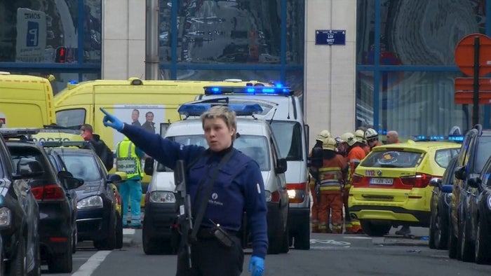 A police woman gestures in front of ambulances at the scene of a blast outside a metro station.