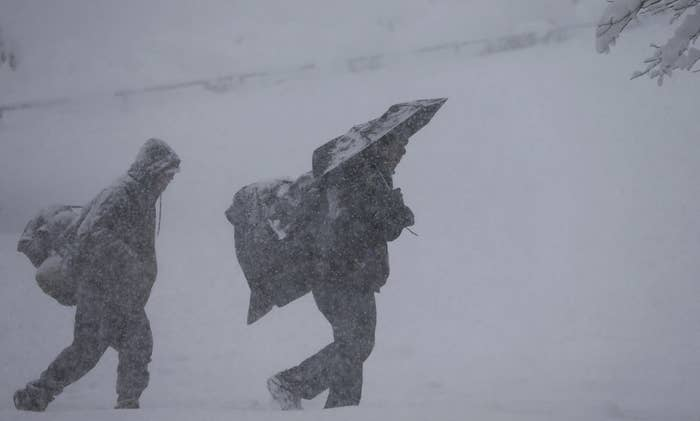 Pedestrians struggle to walk in snow near the State Capitol in Denver.