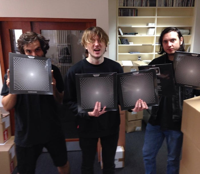 """(From left to right) Jim, Matt, and Mike hold up their new album """"Eleven Eleven"""" and everyone in the world cries because they're so excited."""