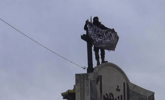 A fighter from Syria's al-Qaida-linked Nusra Front holds his group flag in Idlib province in April 2015