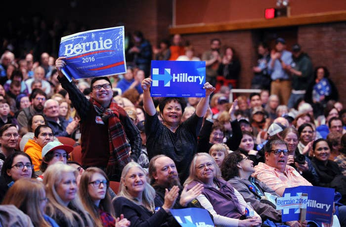Bernie Sanders supporter Stephen Wong, left, and Hillary Clinton supporter Benita Lozano stand up for their candidates at the Democratic party caucus in Anchorage, Alaska Saturday