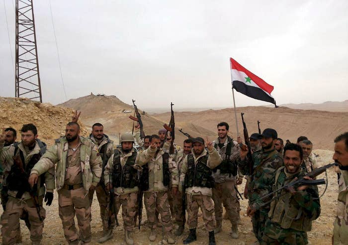 Syrian regime forces flash victory signs and carry a Syrian national flag in Palmyra.