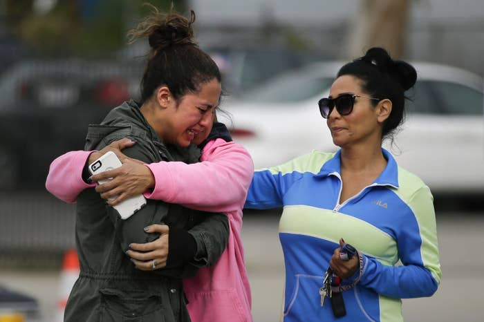 Mourners comfort one another at a makeshift memorial for the victims of the attack in San Bernardino, Calif.