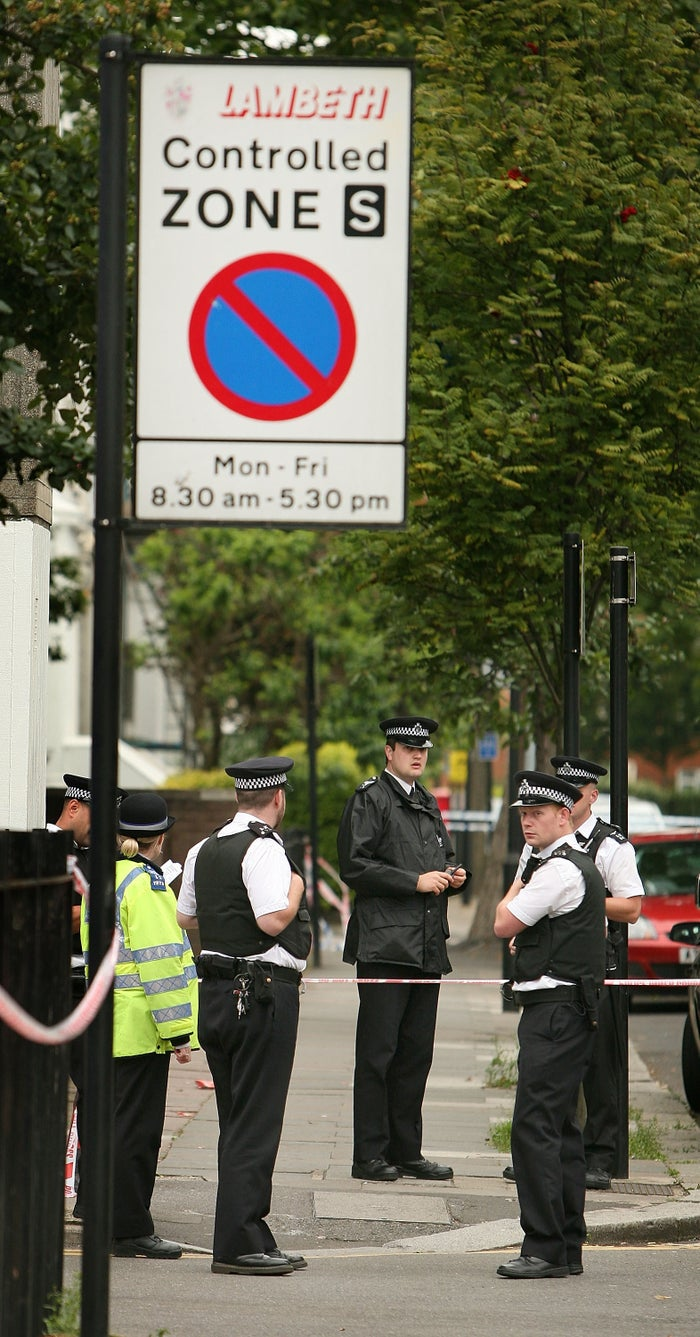 Police officers gather near the scene of the stabbing of an 18-year-old boy in Lambeth on 18 July 2008.