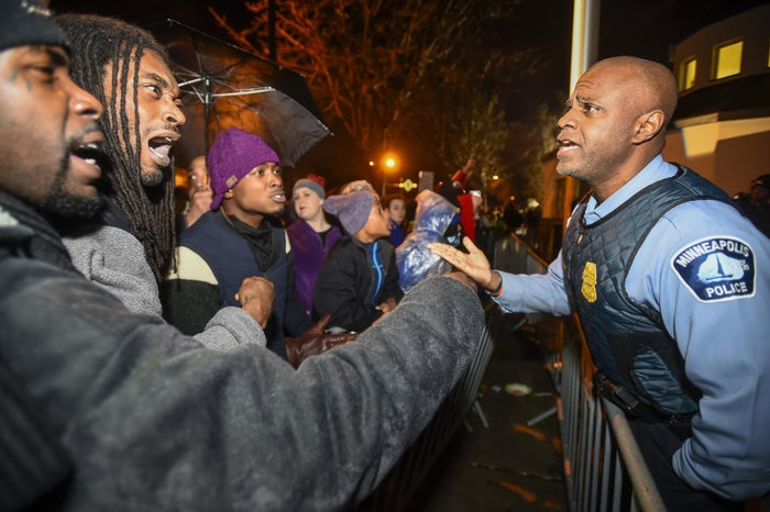 A police officer talks with demonstrators in front of a Minneapolis police precinct during a protest. November 18, 2015.