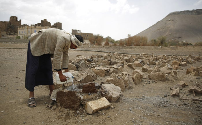 Faisal Ahmed, the father of Udai Faisal, pours water on his son's grave in Hazyaz village, on the southern outskirts of Sanaa.