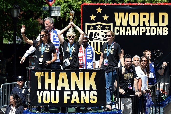 Megan Rapinoe holds the World Cup 2015 trophy on her head during the ticker tape parade in New York on July 10, 2015.
