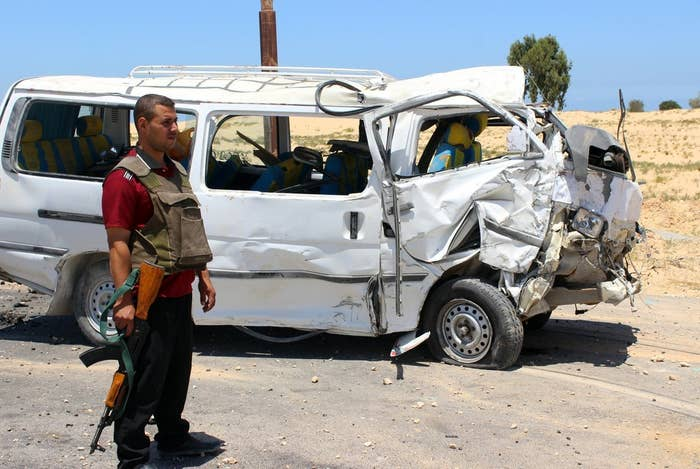 A member of the Egyptian security forces stands next to a damaged bus after a roadside bomb blast on the outskirts of al-Arish.