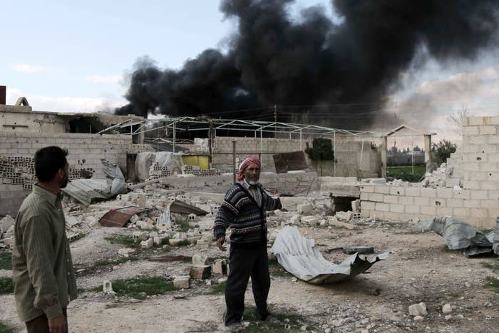 A Syrian man stands in the courtyard of his farm as smoke billows in the background following reported air strikes.