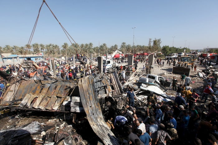 Residents gather at the site of a car bomb attack at a checkpoint in Hillah.