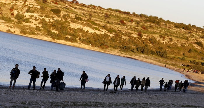 Refugees walk along a Turkish beach before trying to travel to Greece on Saturday.