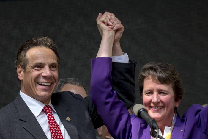 New York State governor Andrew Cuomo raises arms with Mary Kay Henry, president of labor union SEIU, which backs the Fight for 15.
