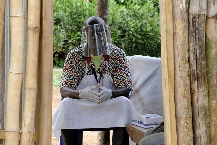 A man wearing a protective helmet as part of a measure to fight against the Ebola virus sits at the entrance of a clinic Grand Gedeh, Liberia, on April 14, 2015.