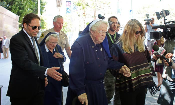 Sisters Catherine Rose Holzman, second left, and Rita Callanan, center, is escorted by businesswoman Dana Hollister.