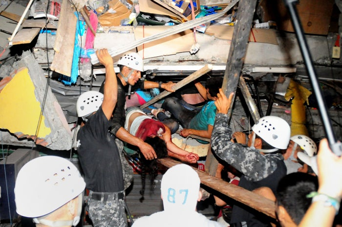 Rescue workers work to pull out survivors trapped in a collapsed building after a huge earthquake struck.