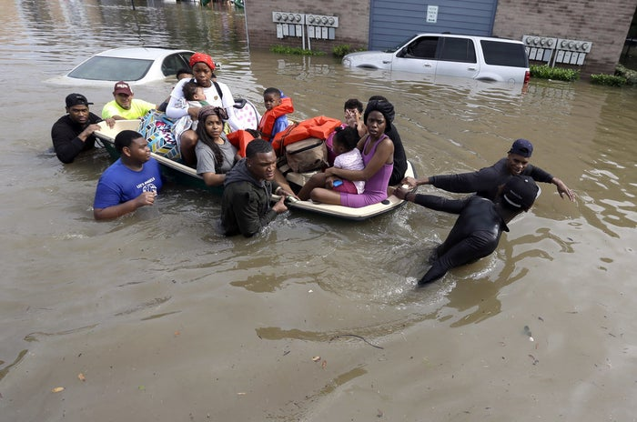 Residents are helped to dry ground as they evacuate an apartment complex in Houston.