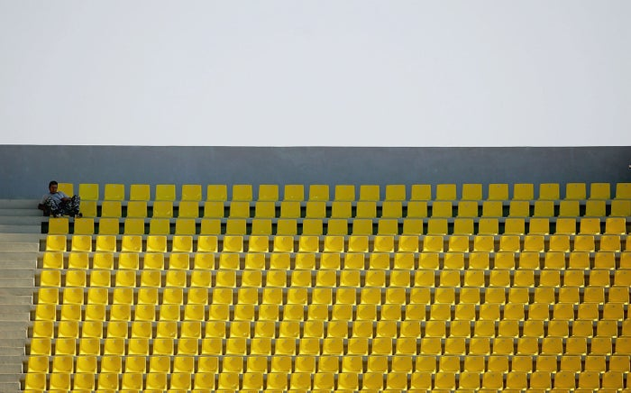 A lone spectator sits in the empty stands during the women's football preliminary match between USA and Australia on August 17, 2004 during the Athens 2004 Summer Olympic Games Thessaloniki, Greece.