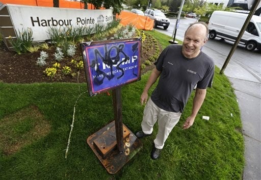 Peter Zieve, in April, poses for a photo with campaign signs supporting Donald Trump on his property that he had reinforced with metal base safter the signs were repeatedly vandalized and tipped over.