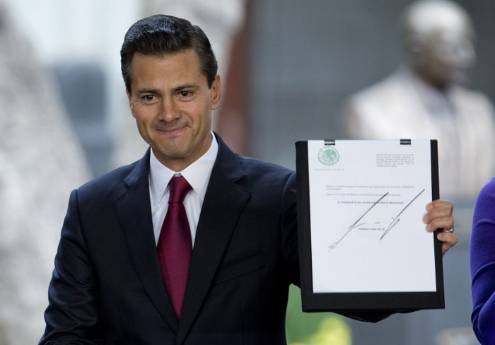 Mexican President Enrique Pena Nieto holds up a signed document during an announcement on proposed marijuana policy, in Mexico City, Thursday April 21, 2016.