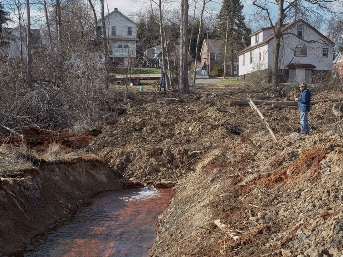Construction surrounds a creek flowing with orange-colored water due to mine drainage in DuBois, Pennsylvania, on Friday, April 1, 2016. Before construction, water would spout out of the ground. It is now being diverted.