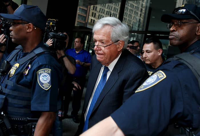 Former U.S. House of Representatives Speaker Dennis Hastert is surrounded by officers as he leaves federal court.