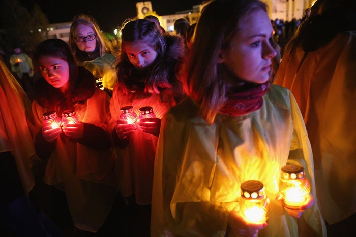 Young people prepare to lay candles in the pattern of a radioactivity symbol shortly before midnight on 25 April 2016 in Slavutych, Ukraine, 50 kilometres (30 miles) from the accident site.