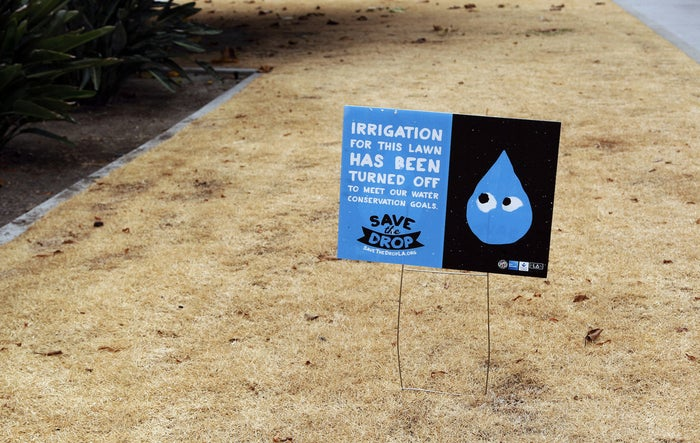 A dried-out lawn at Los Angeles City Hall is seen with a sign explaining that irrigation has been shut off due to the ongoing drought.