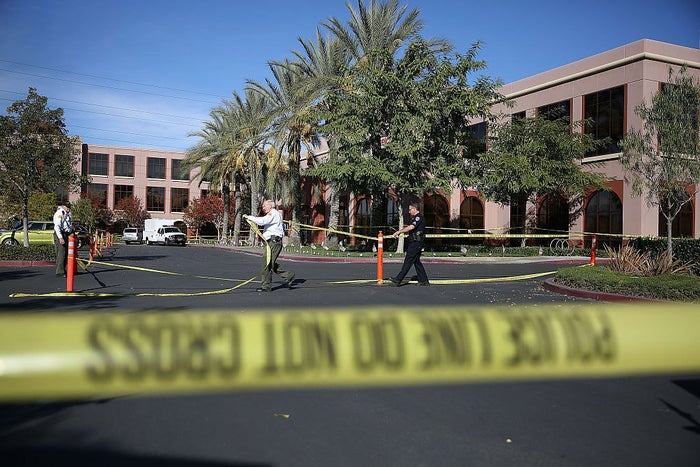 Officials put up police tape in front of the Inland Regional Center where 14 people were killed on Dec. 7, 2015.