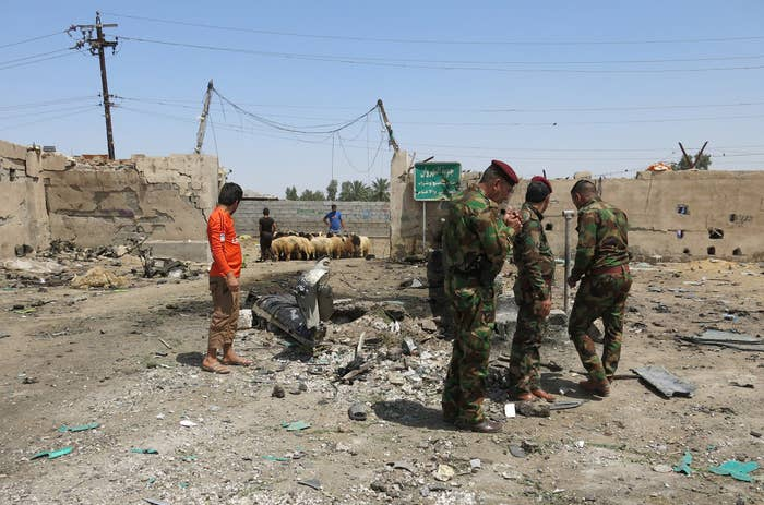 Iraqi security forces stand at the site of the car bomb attack.