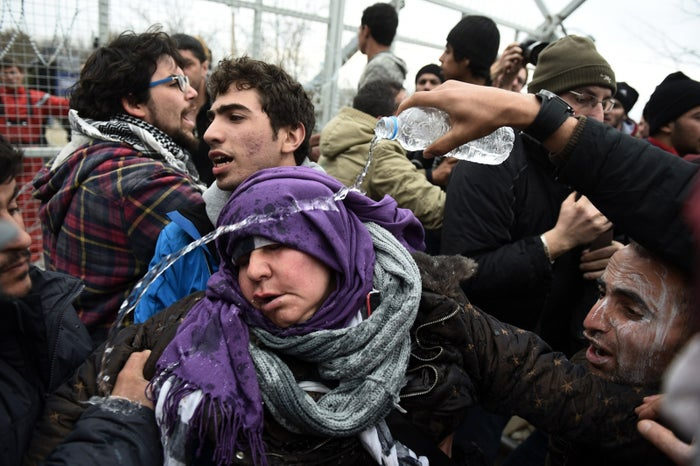 A woman is helped by other refugees and migrants during a protest in front of an iron fence at the Greek-Macedonian border near the northern Greek village of Idomeni on Monday, Feb. 29, 2016. (AP Photo/Giannis Papanikos)