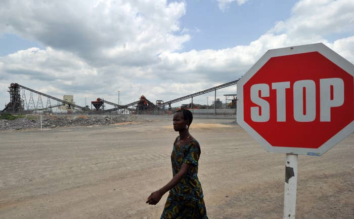 A woman walks past a diamond mining company owned by Israeli diamond magnate Beny Steinmetz in Sierra Leone