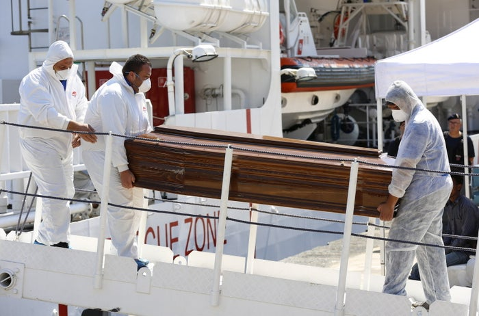A coffin is removed from a Coast Guard ship in a Sicilian harbor Friday.