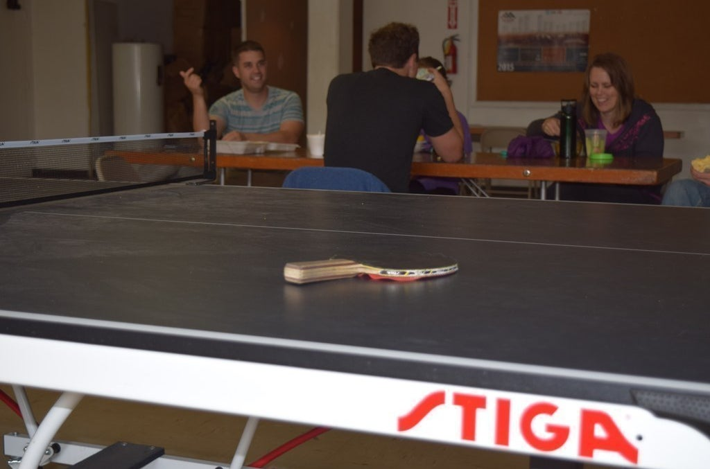 Code bootcamp attendees relax by a ping pong table in the basement of Church & State.