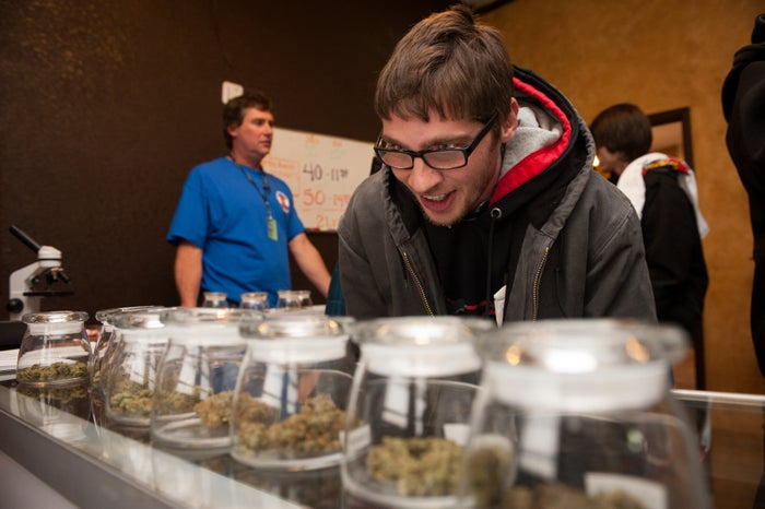 Tyler Williams of Blanchester, Ohio, selects marijuana strains to purchase at the 3-D Denver Discrete Dispensary on Jan. 1, 2014, the first day of legal recreational sales.