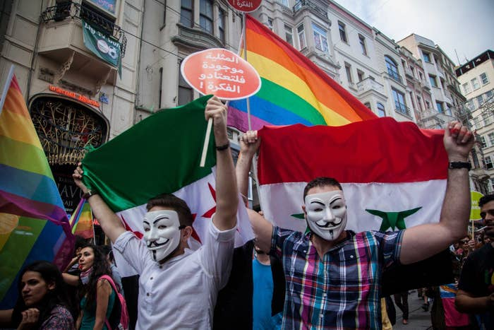 Syrian participants at Istanbul Pride hold both government and opposition flags, with the rainbow flag symbolizing the LGBT community's pride and fight for equality in society, June 30, 2013.