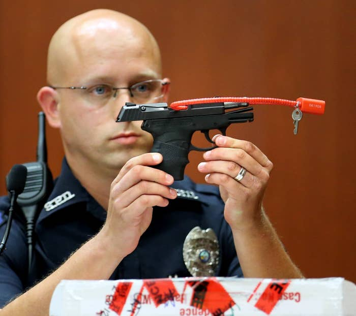 Sanford police officer Timothy Smith holds up the gun that was used to kill Trayvon Martin.