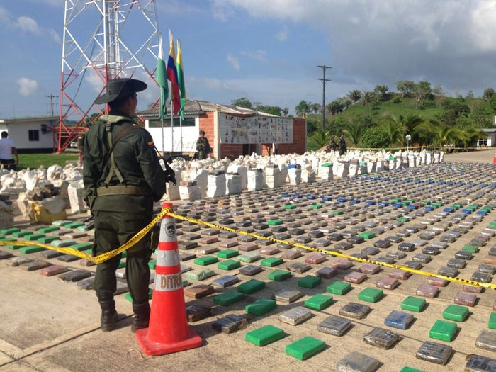 A Colombian national policeman stands guard in front of packages of cocaine.