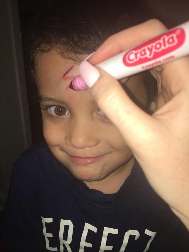 Com um pincel vermelho, Brittaney transformou o corte em um raio. Ayden parecia estar adorando.