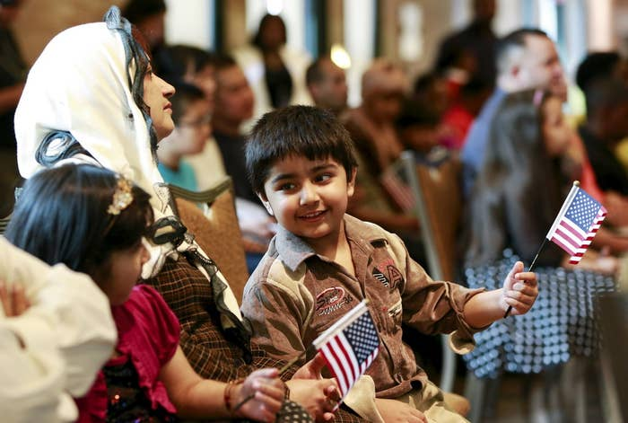 Fiza Kamran, whose parents immigrated from Pakistan, waves a flag during a citizenship ceremony at the Bronx Zoo in New York May 26, 2015.