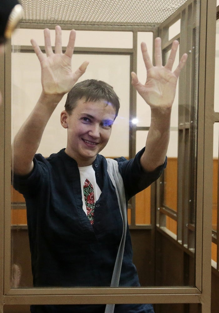 Savchenko waves to journalists from a glass cage in the Russian town of Donetsk on March 21, 2016.
