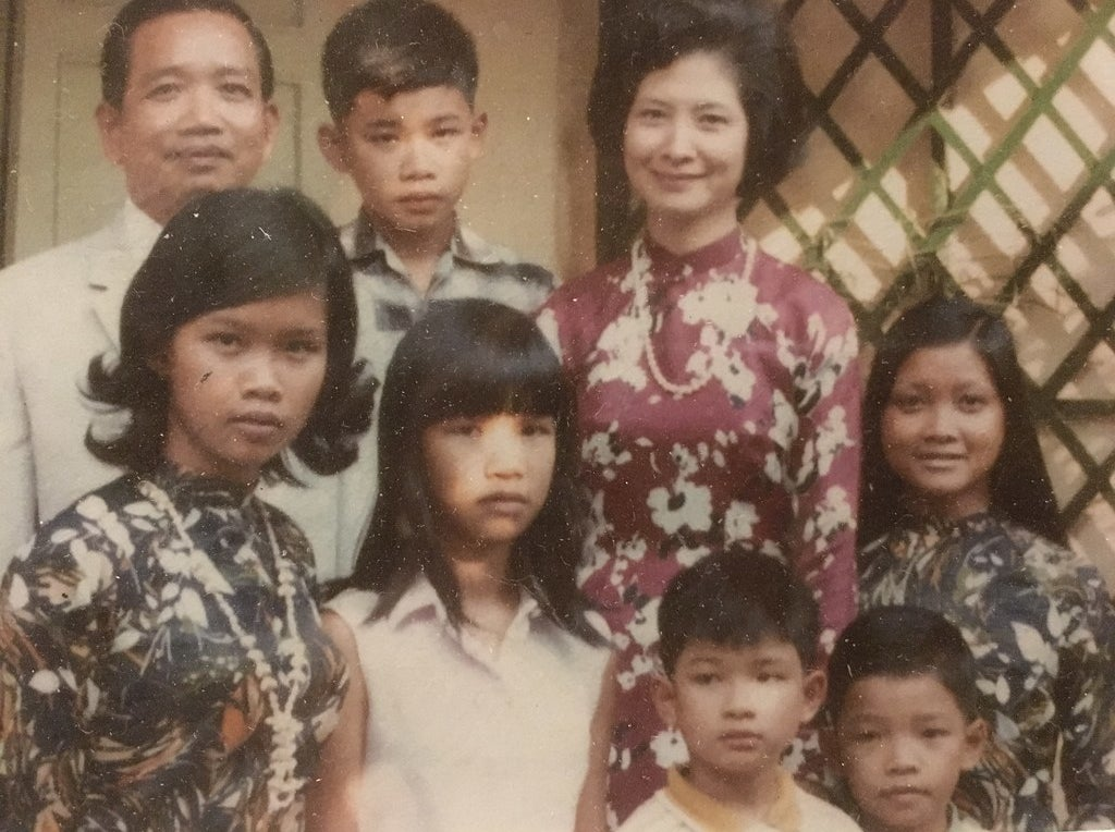 A family portrait (including my father, yellow collar, bottom right) at their home in the the city formerly known as Saigon, in 1968.