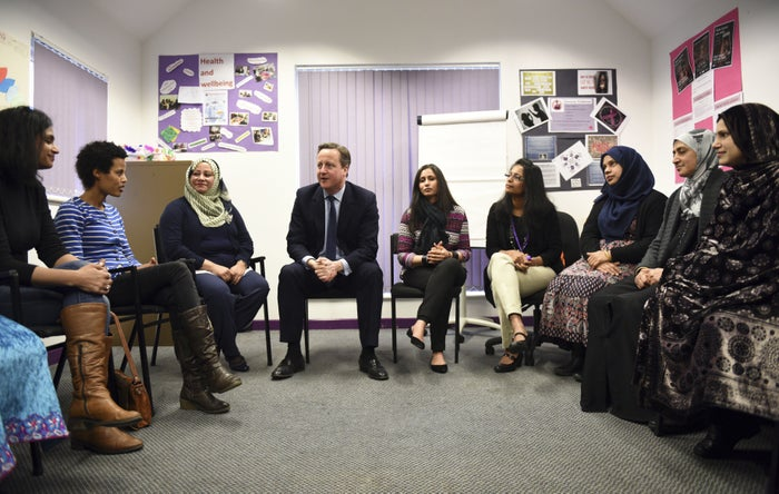 David Cameron speaks with women attending an English language class.