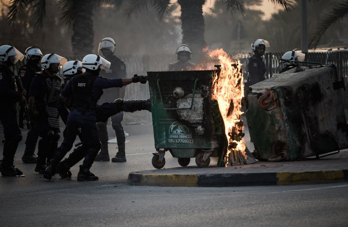 Bahraini riot police push burning bins that were set on fire by protesters in the village of Karranah, west of Manama, on 1 March 2013.