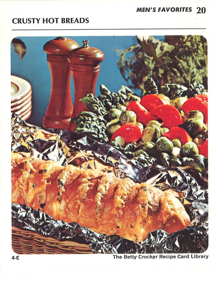 "...Or another dish filed under ""Men's Favorites,"" featuring a little green army of brussel sprouts spying on a loaf of crusty hot bread ensconced in chrome. In the background, salt and pepper loom like a pair of nuclear cooling towers."