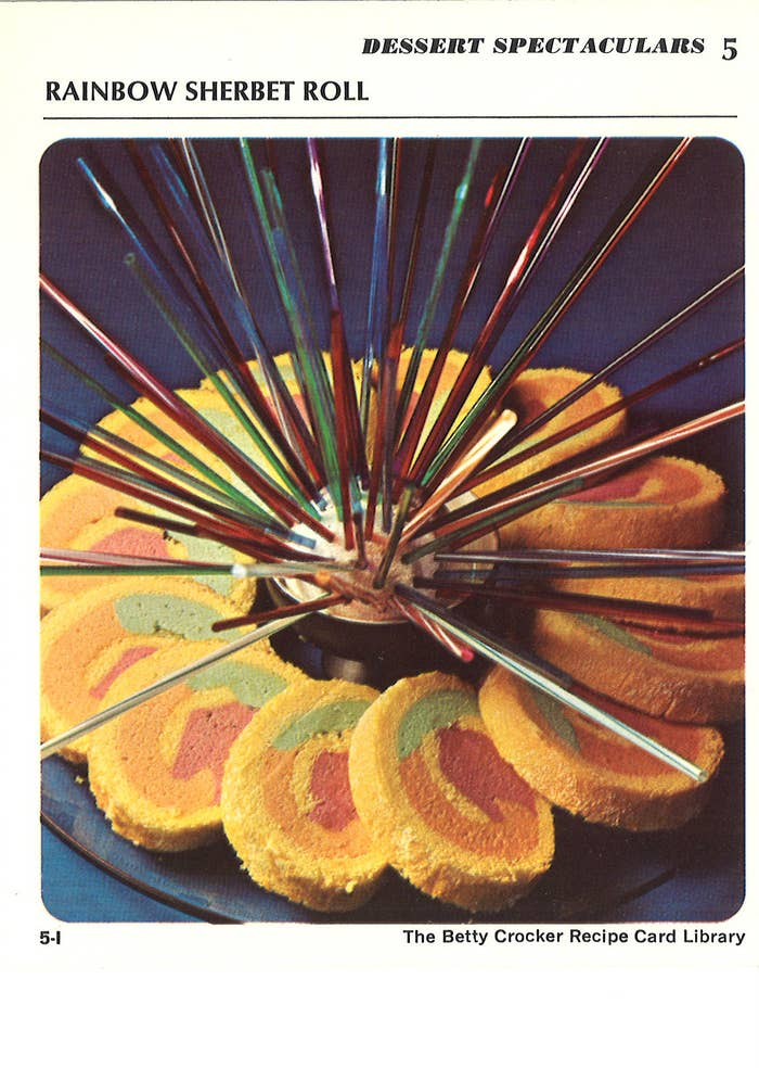 "I was charmed by the enthusiasm behind the titles of the recipes, as if there were nothing more ""Supreme"" than a can of mushroom soup mixed with diced ham. Dazzling also is Betty Crocker's food styling, resembling if your bead curtain took acid then invited you to a picnic on her waterbed. One of the best examples can be found in a colorful confection of rainbow rods radiating from a scoop of sherbet, listed under ""Dessert Spectaculars"":"