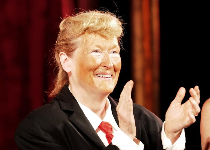 Meryl Streep, in a suit and orange makeup, performs onstage as Donald Trump at the 2016 Public Theater Gala at Delacorte Theater in New York City.