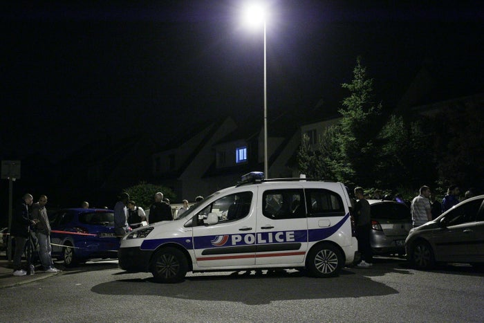 A police vehicle blocks the road Tuesday morning during an assault in the Paris suburb of Magnanville, France.