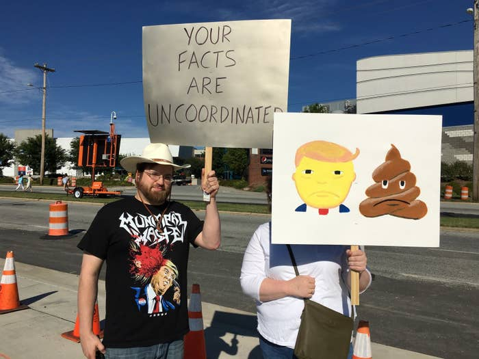 """The sign was the work of Amelia Poovey. The reverse side of the sign read """"chump."""" Poovey was protesting with Adam Casey, left, who when asked why he came out said Trump is """"an orange shambling bag of carbon and water."""""""