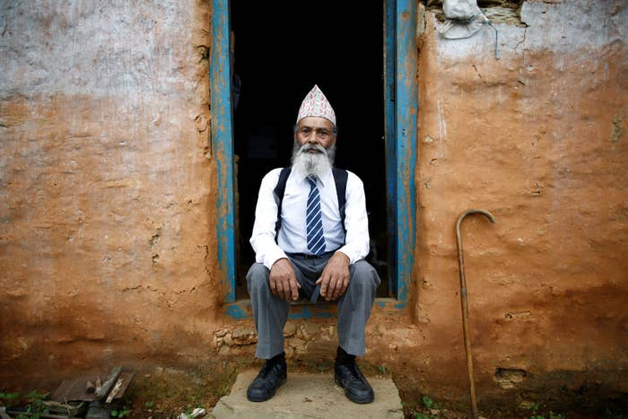 Durga Kami poses for a picture in his school uniform outside his home in Nepal.